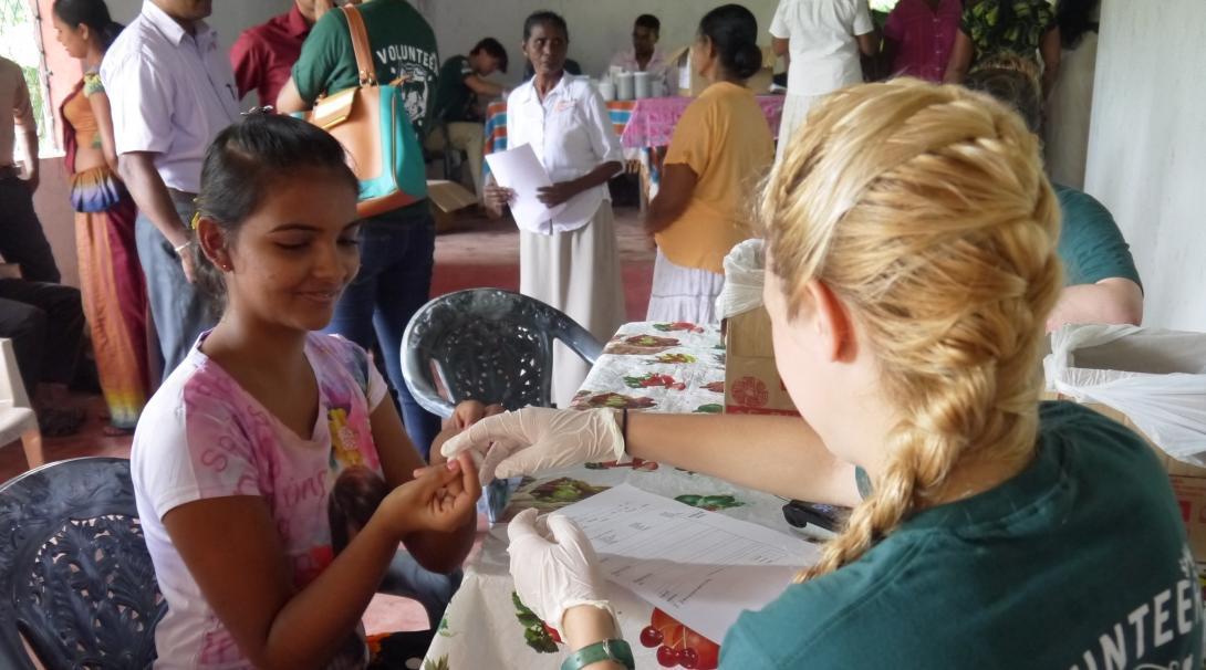 Estudiante de medicina mide los niveles de glucosa durante su pasantía médica en Sri Lanka.